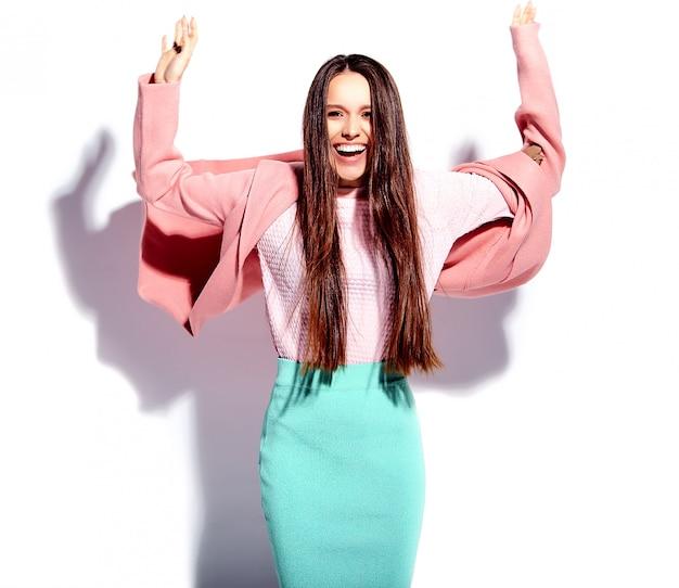 Retrato do modelo de mulher morena sorridente caucasiano bonito no sobretudo rosa brilhante e saia azul elegante de verão