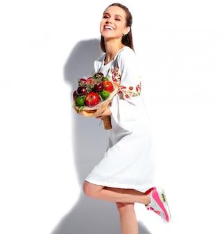 Retrato do modelo de mulher morena sorridente caucasiano lindo vestido elegante verão branco com incomum buquê criativo de flores