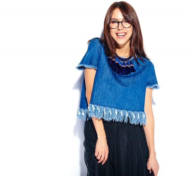 Retrato do modelo de mulher morena sorridente hipster inteligente bonita no casual elegante azul jeans roupas e óculos isolados no branco
