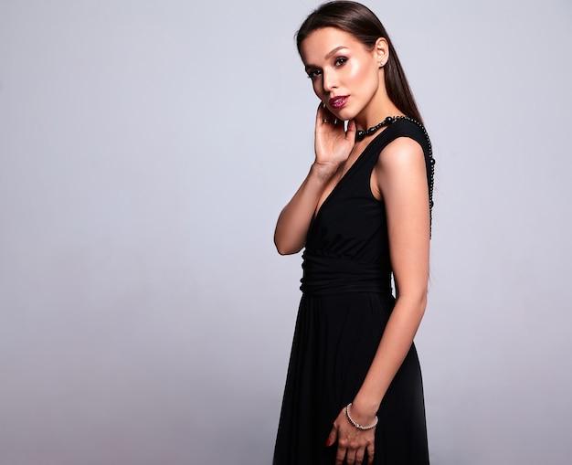 Retrato do modelo de mulher morena sorridente linda de vestido preto com maquiagem de noite ee lábios vermelhos isolados em cinza