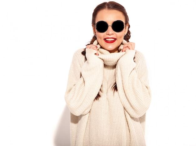 Retrato do modelo de mulher sorridente feliz jovem com maquiagem brilhante e lábios vermelhos com duas tranças em roupas de camisola quente de verão isoladas.