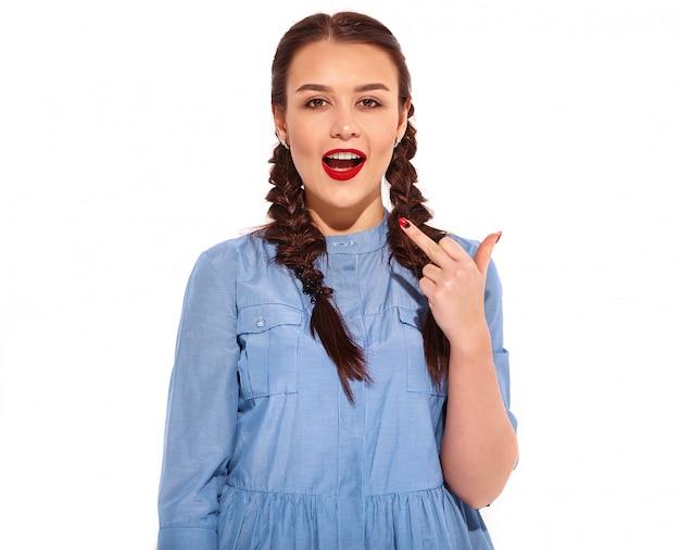 Retrato do modelo de mulher sorridente feliz jovem com maquiagem brilhante e lábios vermelhos com duas tranças nas mãos no vestido azul colorido do verão. mostrando foda-se sinal com o dedo