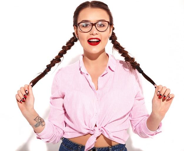 Retrato do modelo de mulher sorridente feliz jovem com maquiagem brilhante e lábios vermelhos com duas tranças no verão colorido rosa camisa amarrada isolada
