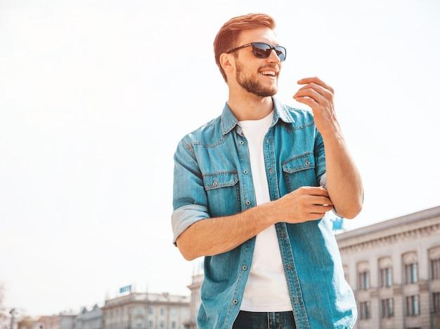 Retrato do modelo de sorriso bonito do homem de negócios lumbersexual do moderno à moda. homem vestido com roupas de jaqueta jeans.