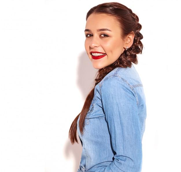 Retrato do modelo de sorriso feliz novo da mulher com composição brilhante e bordos vermelhos com as duas tranças na roupa de calças de ganga do verão isolada.
