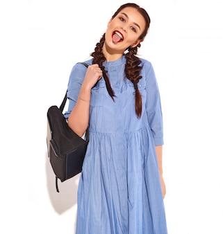 Retrato do modelo de sorriso feliz novo da mulher com composição brilhante e bordos vermelhos com as duas tranças nas mãos no vestido azul colorido do verão e na trouxa isolados. mostrando a língua