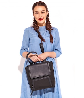 Retrato do modelo de sorriso feliz novo da mulher com composição brilhante e bordos vermelhos com as duas tranças nas mãos no vestido azul colorido do verão e na trouxa isolados.