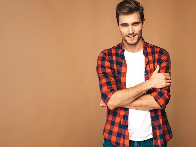 Retrato do modelo elegante jovem sorridente bonito vestido com camisa quadriculada vermelha. homem moda posando. braços cruzados