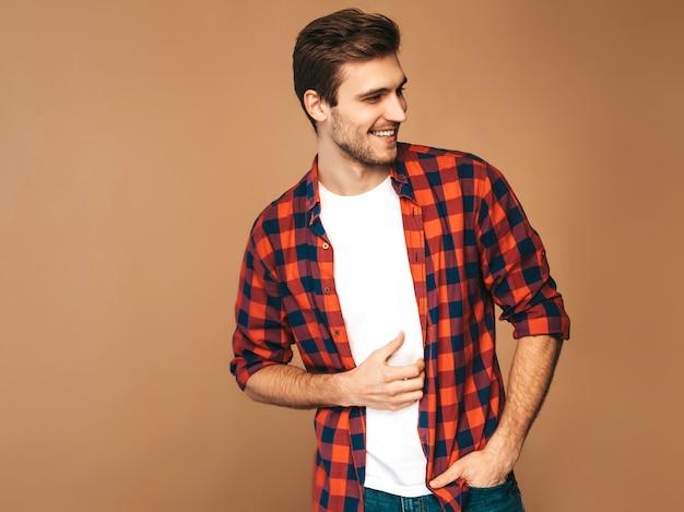 Retrato do modelo elegante jovem sorridente bonito vestido com camisa quadriculada vermelha. homem moda, posar