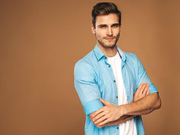 Retrato do modelo elegante jovem sorridente bonito vestido com roupas de camisa azul. homem moda posando. braços cruzados