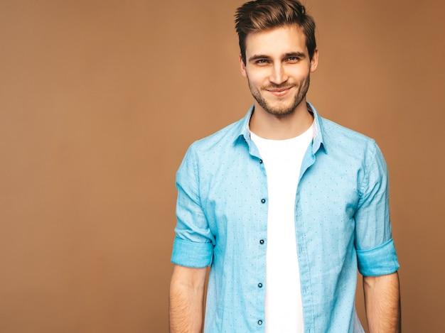 Retrato do modelo elegante jovem sorridente bonito vestido com roupas de camisa azul. homem moda, posar