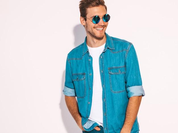Retrato do modelo elegante jovem sorridente bonito vestido com roupas jeans. homem moda usando óculos escuros.