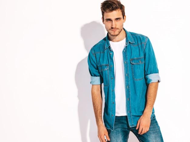 Retrato do modelo elegante jovem sorridente bonito vestido com roupas jeans. homem moda