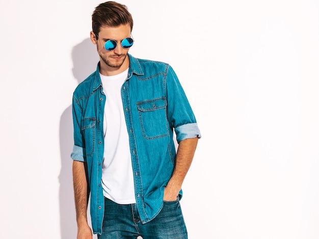 Retrato do modelo elegante jovem sorridente bonito vestindo roupas jeans e óculos de sol. homem moda