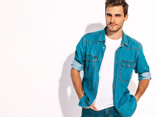 Retrato do modelo elegante jovem sorridente bonito vestindo roupas jeans. homem moda