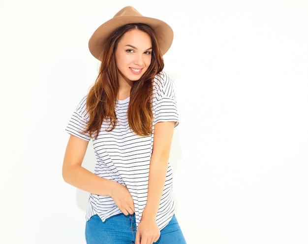 Retrato do modelo jovem elegante em roupas de verão casual com chapéu marrom com maquiagem natural, isolada na parede branca