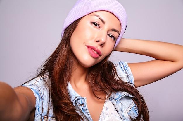 Retrato do modelo linda mulher morena bonita com roupas de jeans casual verão sem maquiagem no gorro roxo, fazendo foto de selfie telefone isolado no cinza