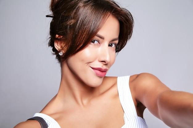 Retrato do modelo linda mulher morena bonita no vestido casual de verão sem maquiagem fazendo foto de selfie telefone isolado no cinza com bolsa