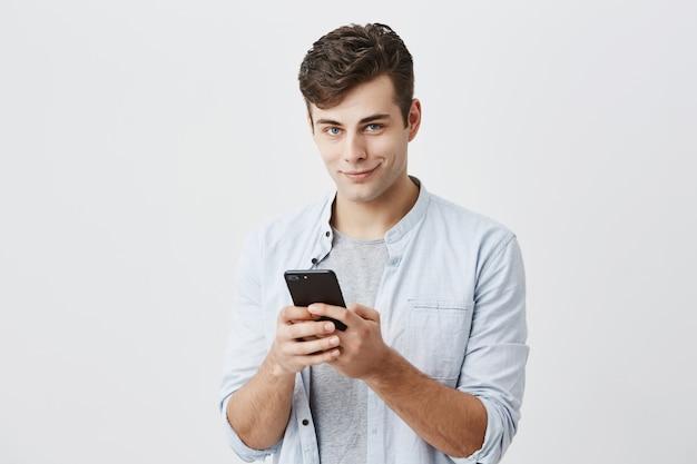 Retrato do modelo masculino bonito atraente, vestindo camisa azul, segurando o telefone inteligente moderno usando a conexão à internet de alta velocidade, mensagens de texto para seus amigos. comunicação e tecnologia moderna.