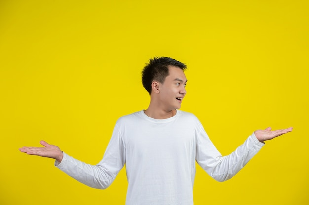 Retrato do modelo masculino espalhando as mãos e sorrindo na parede amarela