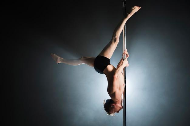 Retrato do modelo masculino forte, realizando uma dança do poste