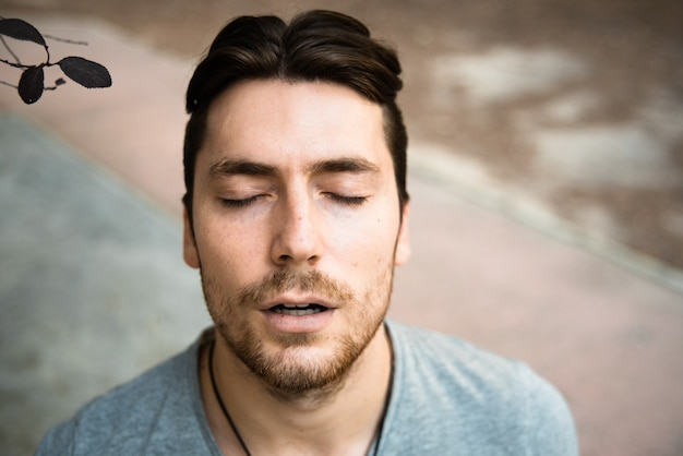 Retrato do modelo masculino jovem atraente de cima, com os olhos fechados e aparência concentrada.