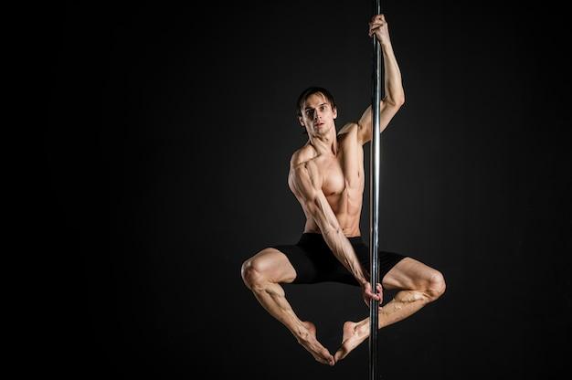 Retrato do modelo masculino, realizando uma dança do poste