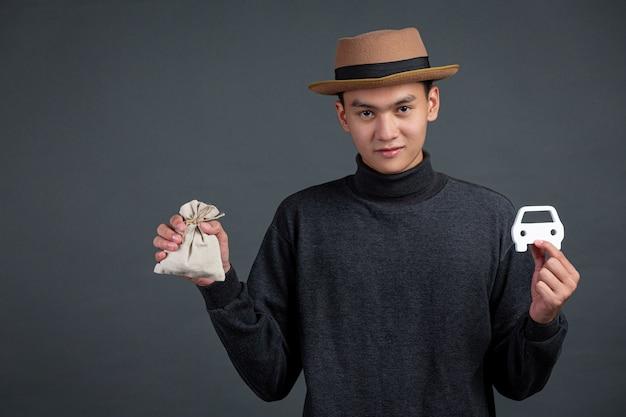 Retrato do modelo masculino segurando um saco de moedas e o modelo do carro na parede escura