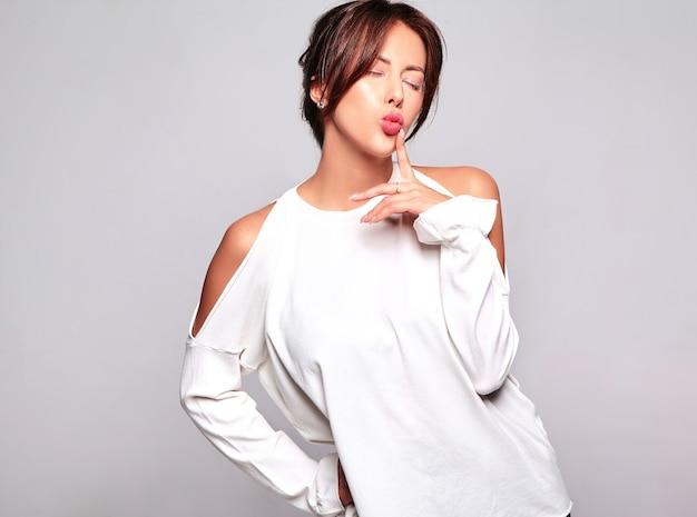Retrato do modelo moreno bonito bonito da mulher na roupa ocasional do verão sem a composição isolada no cinza. dando beijo no ar