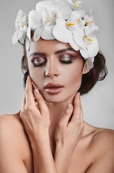 Retrato do modelo moreno bonito, glamouroso e sensual com flores