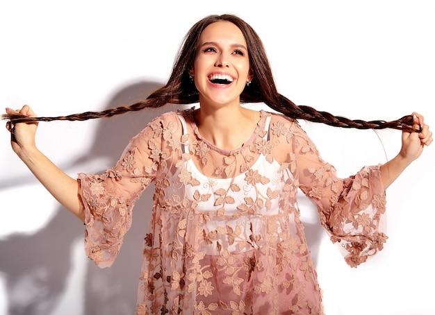 Retrato do modelo moreno de sorriso caucasiano bonito da mulher na roupa à moda do verão cor-de-rosa brilhante isolada no fundo branco.