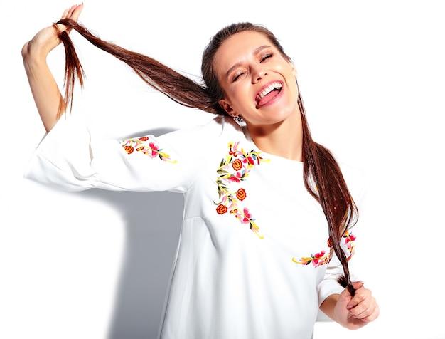 Retrato do modelo moreno de sorriso caucasiano bonito da mulher no vestido à moda do verão branco isolado no fundo branco. torcendo o cabelo dela