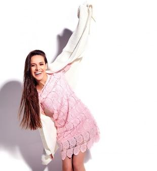 Retrato do modelo moreno de sorriso caucasiano bonito da mulher no vestido à moda do verão cor-de-rosa brilhante isolado no fundo branco. a comemorar