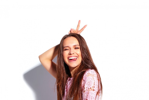 Retrato do modelo moreno de sorriso caucasiano bonito da mulher no vestido à moda do verão cor-de-rosa brilhante isolado no fundo branco. mostrando sua língua e sinal de paz