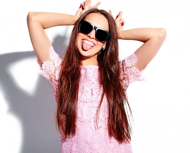 Retrato do modelo moreno de sorriso caucasiano bonito da mulher no vestido à moda do verão cor-de-rosa brilhante nos óculos de sol isolados no fundo branco. mostrando a língua