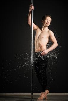 Retrato do modelo profissional masculino, realizando uma dança do poste