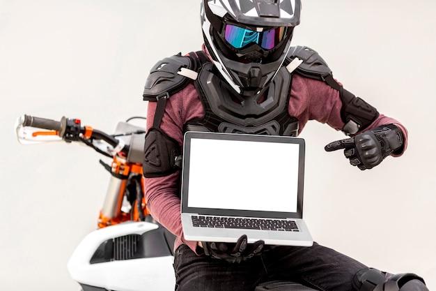 Retrato do motociclista elegante com laptop