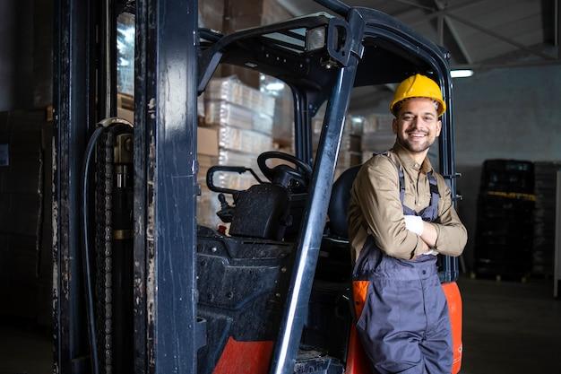 Retrato do motorista de empilhadeira do armazém em pé no armazém perto da máquina.