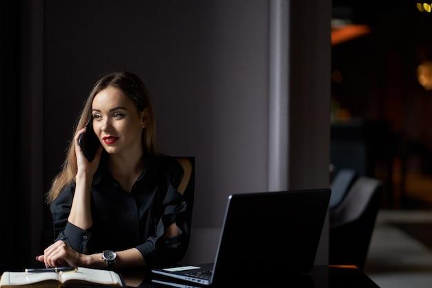 Retrato do negócio da jovem mulher consideravelmente à moda positiva com o laptop que senta-se no local de trabalho e que fala ao telefone.
