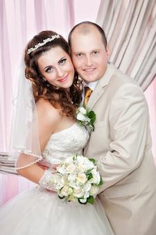 Retrato do noivo e a noiva perto de uma janela