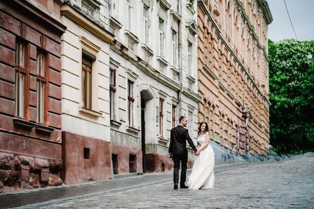 Retrato do noivo e a noiva voltando perto de um prédio antigo, casa velha fora, ao ar livre. recém-casados caminham pelas ruas da cidade de lviv.