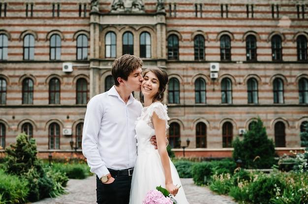 Retrato do noivo e da noiva estão de pé e se abraçando, beijando perto de um prédio antigo do lado de fora, o palácio vintage ao ar livre. romântico. amor na rua.