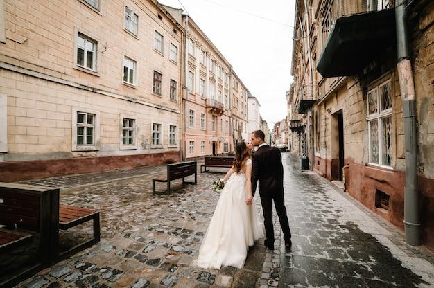 Retrato do noivo e da noiva voltando e se beijando perto de um prédio antigo, casa velha do lado de fora, ao ar livre. recém-casados caminham pelas ruas da cidade de lviv. passeios de casamento.