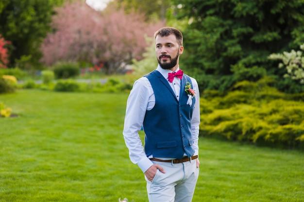 Retrato do noivo elegante sério ao ar livre