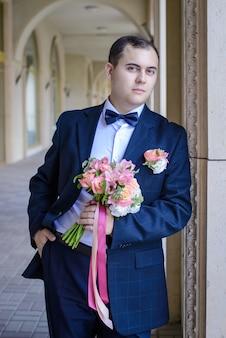 Retrato do noivo em um belo terno elegante com uma gravata borboleta e o buquê de casamento nas mãos no fundo das galerias em arco