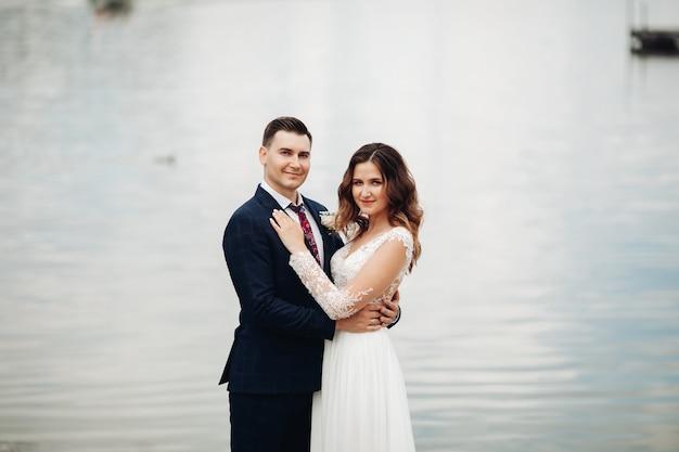 Retrato do noivo em um terno preto com uma linda noiva em um vestido branco no parque fica perto do lago