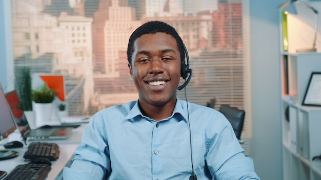 Retrato do operador de serviço ao cliente preto em um fone de ouvido sorrindo para a câmera