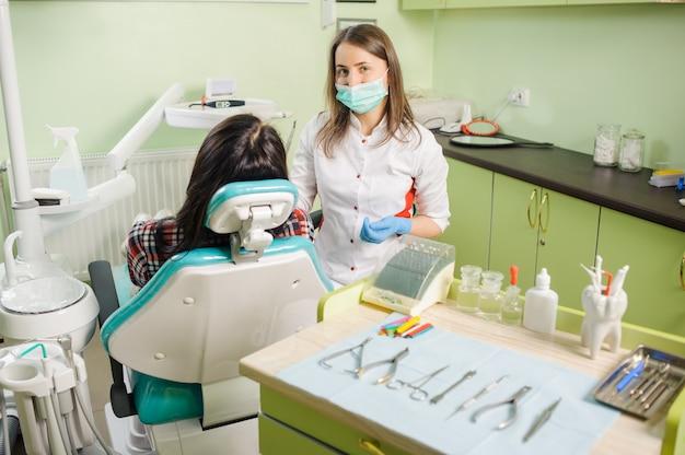 Retrato do ortodontista fêmea de sorriso novo com paciente.