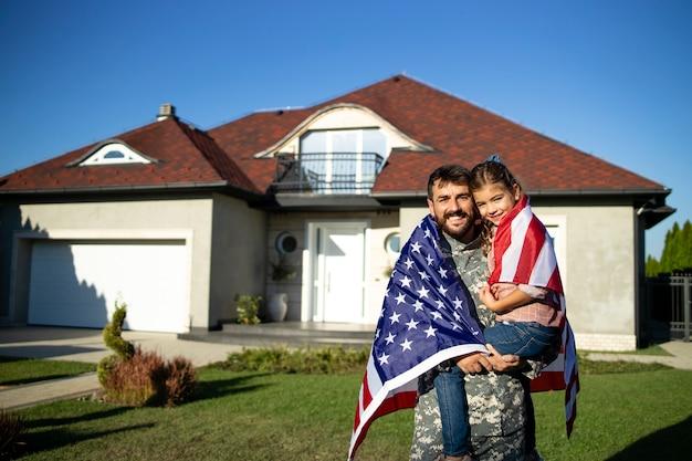 Retrato do pai soldado em licença militar, segurando sua linda filha na frente de sua casa.