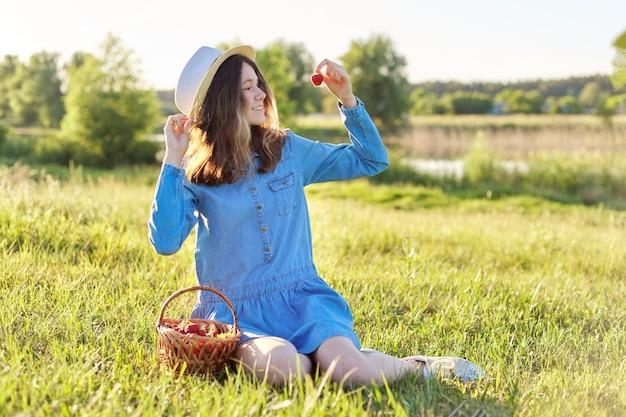 Retrato do país da bela adolescente com chapéu vestido jeans com cesta de morangos frescos, comer morango maduro. fundo de paisagem natural, prado verde, céu azul